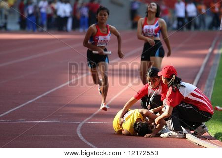 KUALA LUMPUR - AUGUST 18: Malaysia's visually impaired relay team runner falls after her run at the track and field event of the fifth ASEAN Para Games on August 18, 2009 in Kuala Lumpur, Malaysia.