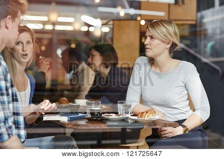 Three friends on a coffee break together sitting and talking in a busy modern cafe, as seen through the window.