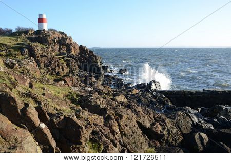 Waves crash against the rocky shore at Aberdour