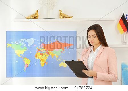 Happy young woman with pen and paper holder in the office of travel company
