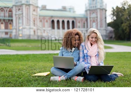 Young girls with laptop outdoors