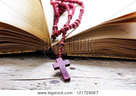 catholic wooden rosary beads with cross in an old open book on rustic wood, religious symbol concept