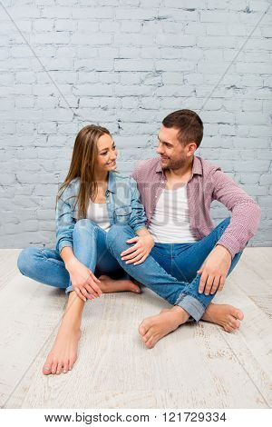Man and woman sitting on the floor and looking on each other with love