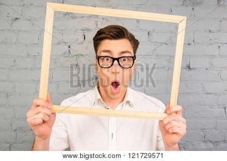 Shocked man in glasses grimacing with open mouth inside fraime