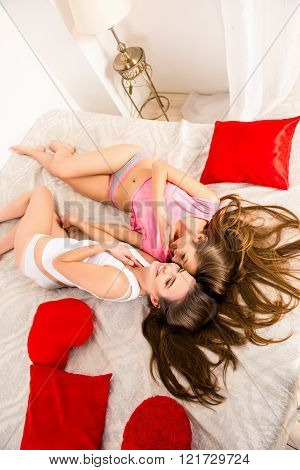 Cheerful girls in pajamas gossiping and lying on the bed holding hands