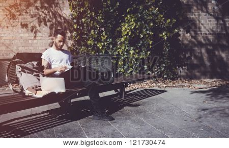 Young man wearing white tshirt sitting city park and reading book. Studying at the University, worki