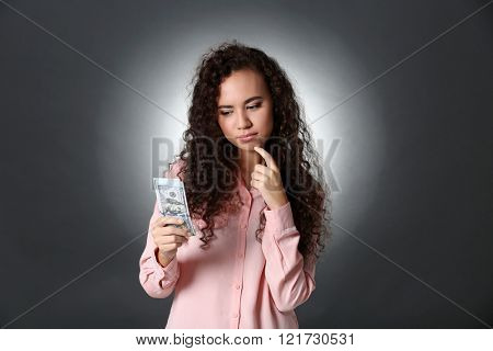 Beautiful young girl holding cash on grey background