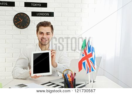 Young man showing tablet in the office of travel company