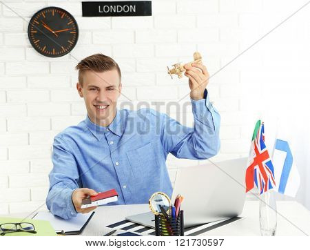 Young man holding passports with tickets and small plane in the office of travel company