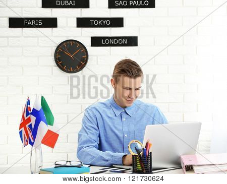 Young man using laptop in the office of travel company