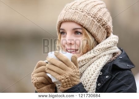 Beautiful girl enjoying a cup of tea outdoors