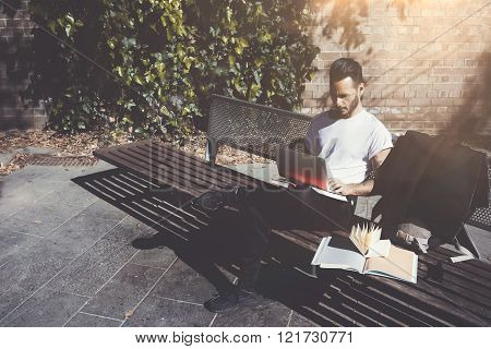 Photo man sitting city park bench and texting message notebook. Using wireless internet. Studying at
