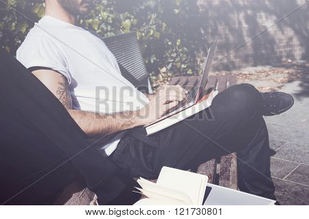 Photo man sitting city park bench and working laptop. Using wireless internet. Studying at the Unive