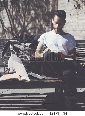 Bearded student wearing white tshirt sitting city park and draws notepad. Studying at the University
