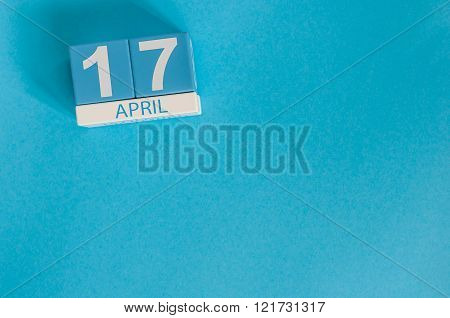 April 17th. Image of april 17 wooden color calendar on blue background.  Spring day, empty space for