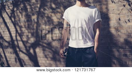 Photo young serious man with tattoo wearing blank white tshirt. Stands in front of a brick wall. Cit
