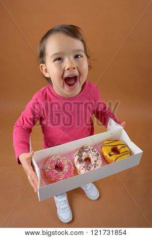 Little girl with sweet different types of donuts