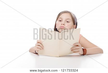 A preteen girl reads a book on white