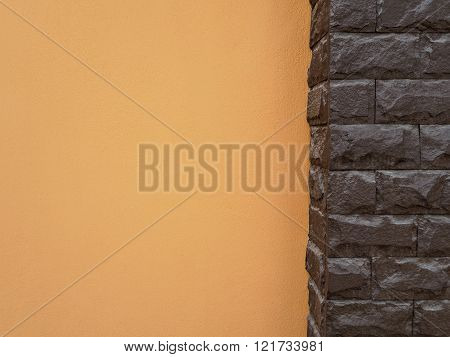 Dark brown stone pole and orange cement wall