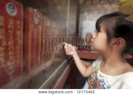 MALACCA - FEBRUARY 16: Young girl pays homage and offer a silent prayer to deceased relatives at the temple during Chinese New Year celebrations in Malacca. February 16, 2010 in Malacca, Malaysia.