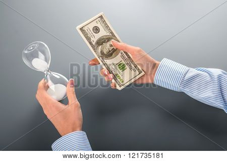 Businesswoman holding money and hourglass.