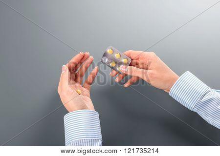 Female taking pill from blister.