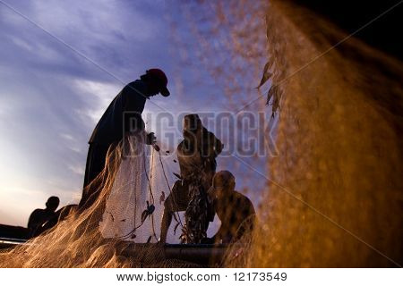 BALI - JANUARY 16: Life in a fishing village, fishermen repair nets at dusk at Jimbaran village, Bali January 16, 2010 in Bali, Indonesia.