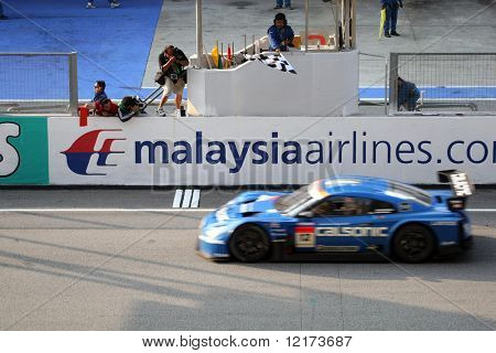 SEPANG, MALAYSIA - JUNE 21: The Calsonic Impul GTR Nissan car (12) taking the checkered flag winning the GT500 race of the Super GT International Series Round 4 race. June 21, 2010 in Sepang Malaysia.