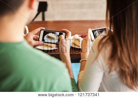 Couple taking photos of their dessert