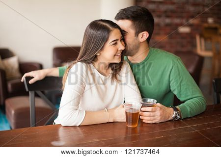 Man Whispering To A Girl At The Bar