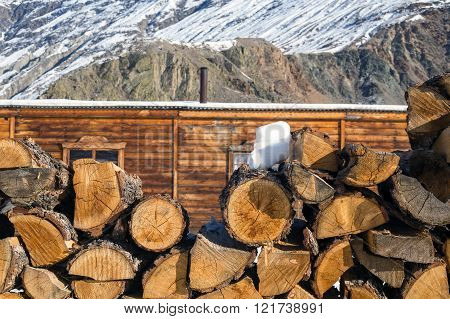 Stack of firewood at mountains background. Rural scene.
