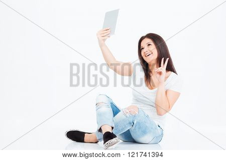 Smiling casual woman video chatting with tablet computer isolated on a white background