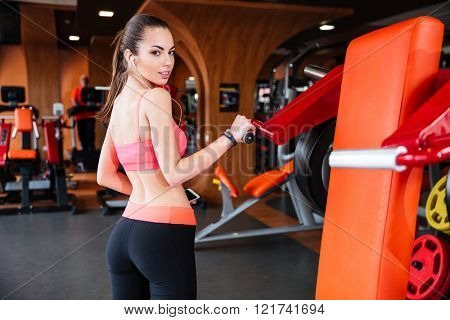 Pretty young sportswoman listening to music and training in gym