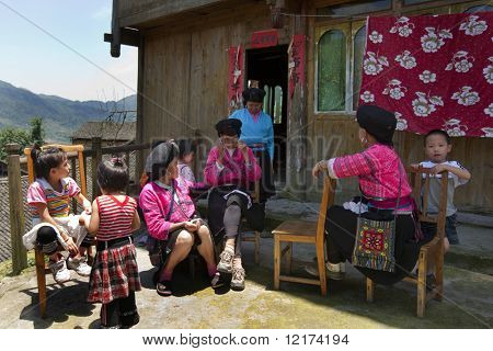 GUILIN, CHINA - MAY 23: Farm womenfolk and children rest in front of their home in Longji on May 23, 2010. The traditional costumes and lifestyle make Lingji a popular tourist destination.