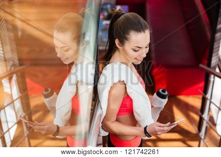 Smiling pretty young sportswoman drinking water and using smartphone in gym