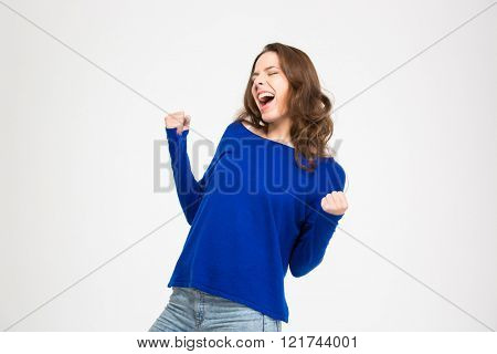 Excited delighted young woman shouting and celebrating success over white background
