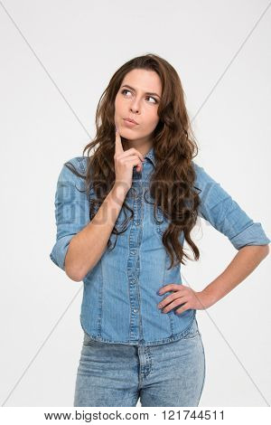 Pensive attractive young woman standing and thinking over white background
