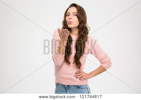 Lovely charming young woman in pink sweatshirt standing and sending a kiss over white background