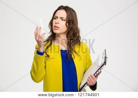 Confused pretty young woman in yellow jacket holding folders with documents and using smartphone over white background