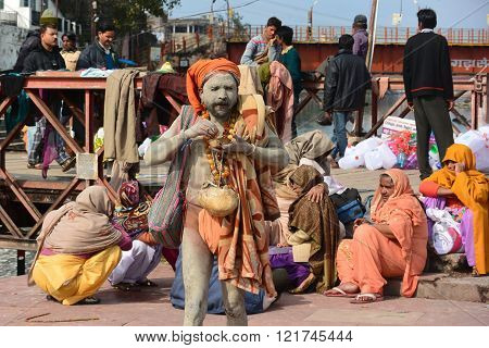 HARIDWAR, INDIA - MARCH 1, 2014: Sadhu Hindu holy man covered in ashes is eating.  Female pilgrims dressed in colorful Saris sit behind him.  Men in background look at the Ganges River in Holy City Haridwar
