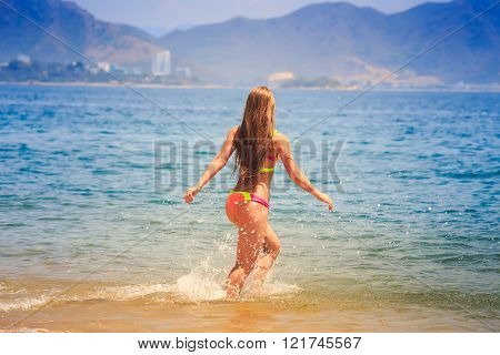 Blonde Slim Girl In Bikini Runs Into Sea Splashes Against Hills