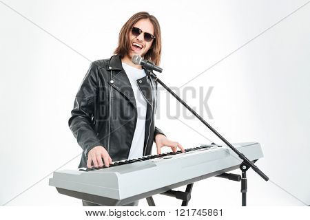 Happy attractive young man in sunglasses with long hair singing in microphone and playing on synthesizer over white background