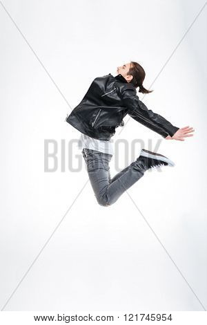 Profile of attractive young man in black leather jacket jumping high over white background