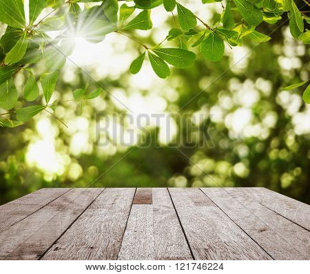 Wood table top on green leaf with light bokeh and over light the sun on green blurred background Can used for display or montage your products