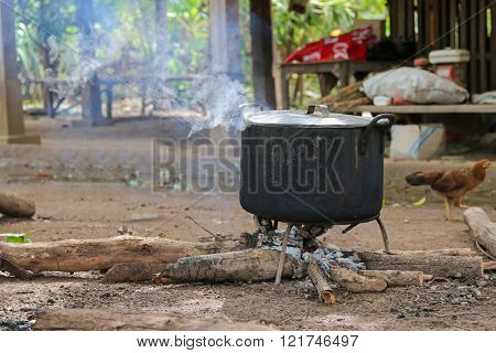Hot steam coming out through lid on black boiling pot above wood fire on the ground in Laos