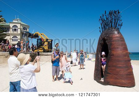 COTTESLOE,WA,AUSTRALIA-MARCH 12,2016: Families enjoying photo-ops with wood and metal sculpture at the interactive public arts festival Sculptures By The Sea at Cottesloe Beach in Cottesloe, Western Australia.