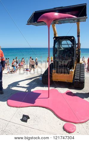 COTTESLOE,WA,AUSTRALIA-MARCH 12,2016: Backhoe dripping pink sculpture and tourists enjoying the interactive public arts festival Sculptures By The Sea at Cottesloe Beach in Cottesloe, Western Australia.