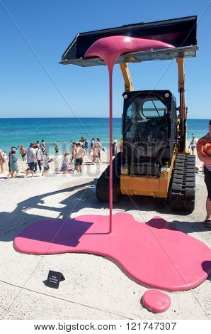 COTTESLOE,WA,AUSTRALIA-MARCH 12,2016: Backhoe sculpture oozing pink and tourists enjoying the interactive public arts festival Sculptures By The Sea at Cottesloe Beach in Cottesloe, Western Australia.