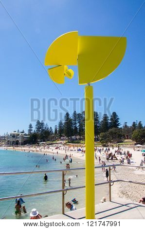 COTTESLOE,WA,AUSTRALIA-MARCH 12,2016: Rotating bright yellow sculpture with tourists at the