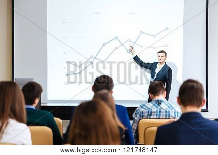 Smiling handsome speaker standing and explaining graphs on business conference in meeting hall